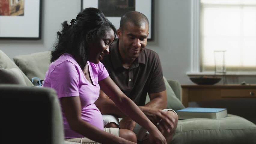 Medium Shot Close Up Pregnant woman and man sitting on sofa and looking at baby clothing