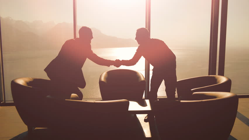 Handshaking businessman. meeting. businessman conversation. discussion talking. silhouette. business background. company career corporate. cooperation. professionals. sunset sun flare. luxury interior