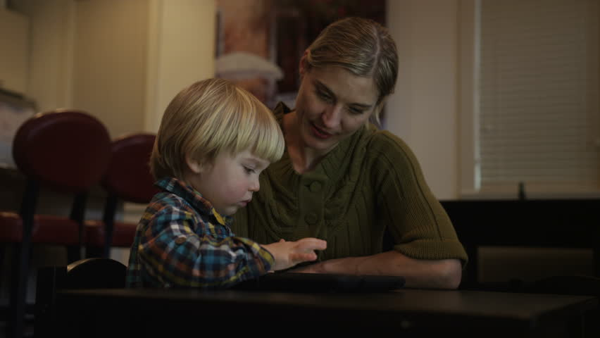 A young boy uses a tablet and his mother talks about the nine eggs he sees on the screen.