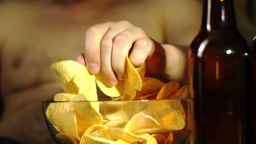 Close-up of a table with bottles of beer and a bowl of potato chips. Man in the background drinking a beer, and then reaches out, takes chips