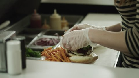 Medium Shot Waitress preparing and serving sandwiches in diner