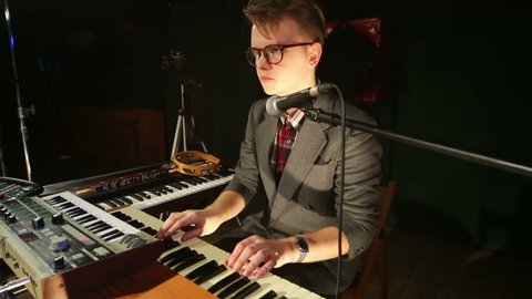 Handsome man in glasses plays synthesizer in night club with smoke