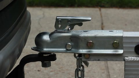 Putting trailer on ball hitch. Lifting trailer on ball hitch and securing locking device.