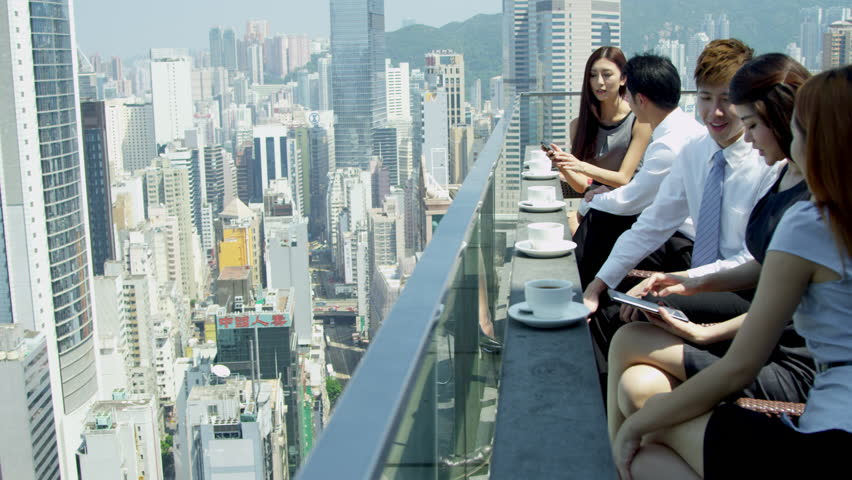 Group young male female Asian Chinese advertising managers drinking coffee using wireless tablets rooftop restaurant modern cityscape background shot on RED EPIC | Shutterstock HD Video #6435029