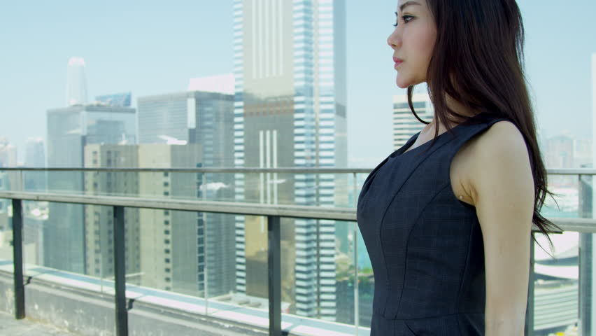 young female asian chinese financial consultant modern city skyscraper rooftop smiling to camera portrait shot on red epic stock footage video 6435206 - Epic Consultant