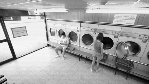 High Angle LS CCTV Style A Young Man and a Young Woman use their Launderette