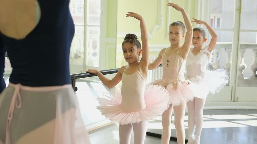 Female Ballet Dancer stands before a trio of young Ballerinas demonstrating the movements and encouraging leg and arm extension | Shutterstock HD Video #6441026