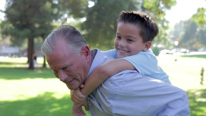 Grandfather Giving Grandson Piggyback Ride Through Park