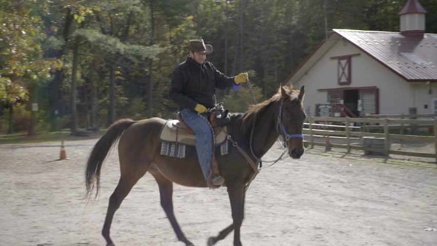 A man rides his horse around his farm