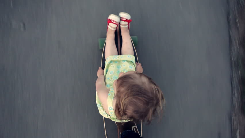 Little girl sits on a longboard, which is run by her dad. View from above. | Shutterstock Video #6482549
