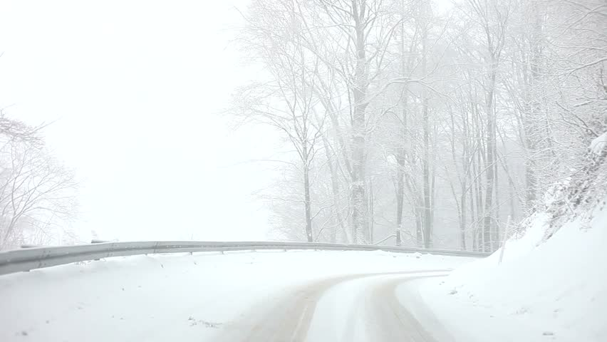 Car driving on Snow Blizzard on winter snow forest road