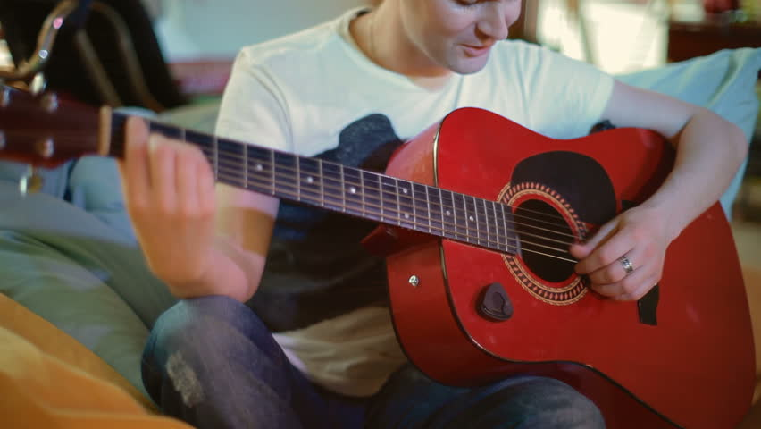 Young Attractive Man Sitting Playing Guitar