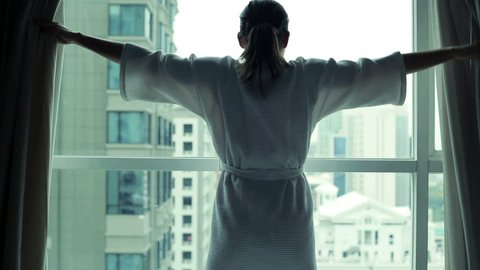 woman unveil curtains and looking through the window at cityscape view