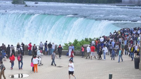 NIAGARA FALLS, CANADA - Circa June, 2014 - Tourists gather at an overlook at Niagara Falls in the Canadian side.  For editorial use only.