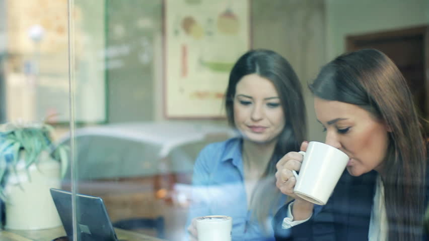 Young businesswomen and businessman talking during coffee break in cafe