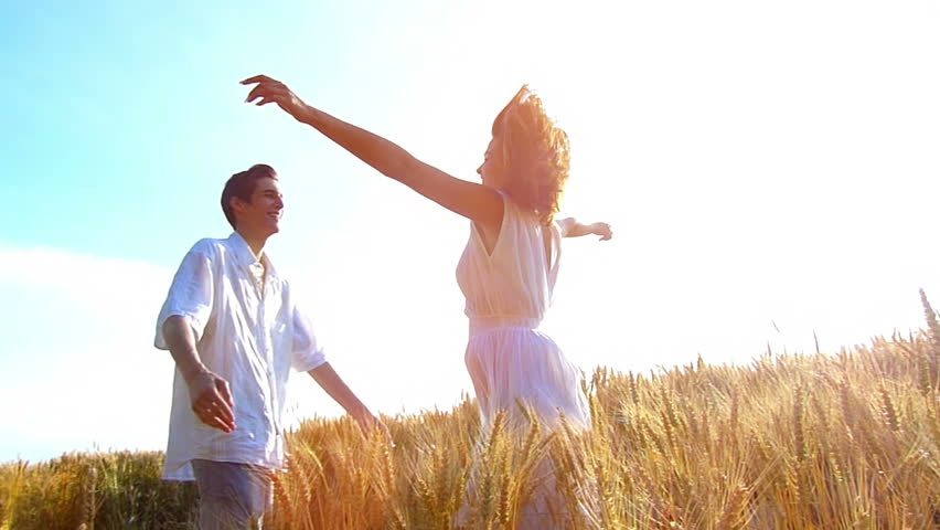 Young ,happy woman run into the arms of her boyfriend, love in the wheat field at sunset.Flare light, slow motion, high speed camera, flare light