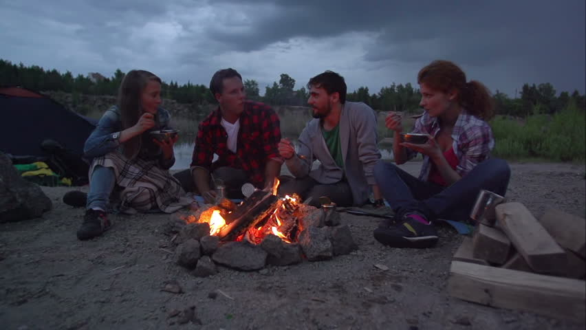 Pan of four friends having meal at fireside in slow motion