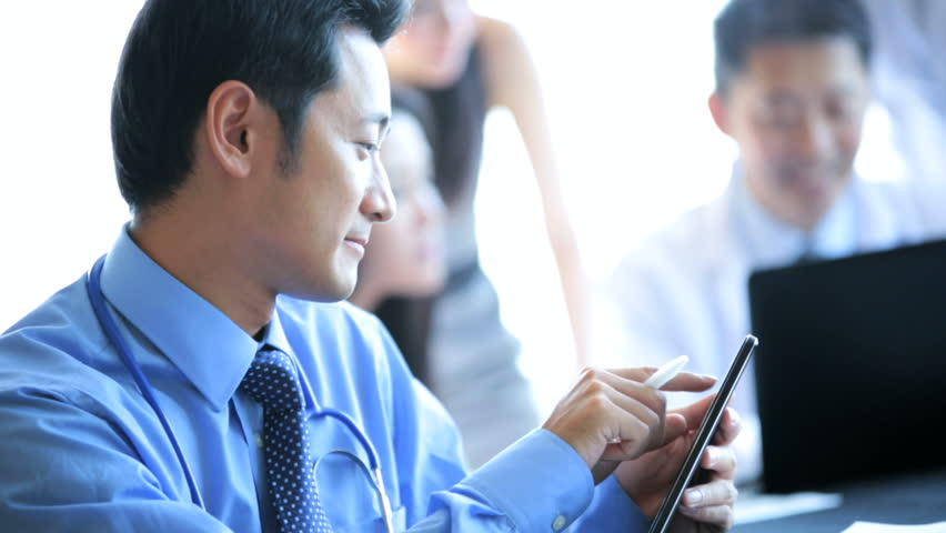 Male female Asian Chinese medical executives doctors meeting modern hospital boardroom portrait male doctor foreground | Shutterstock HD Video #6670256