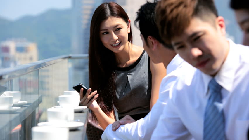 Close up young male female Asian Chinese advertising managers talking drinking coffee rooftop restaurant modern cityscape background | Shutterstock HD Video #6676286
