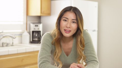 Asian woman looking at camera and chatting while sitting in kitchen