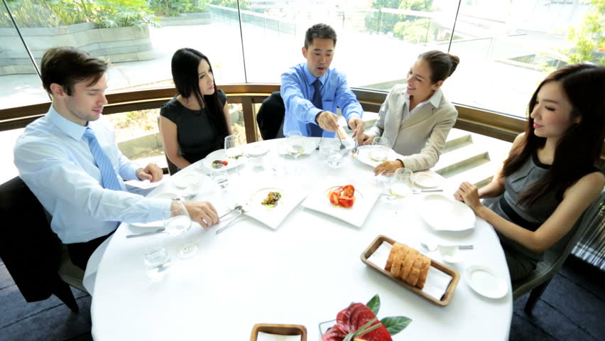 Successful male female Asian Chinese Caucasian advertising executives meeting working lunch downtown city restaurant elevated view | Shutterstock HD Video #6677810