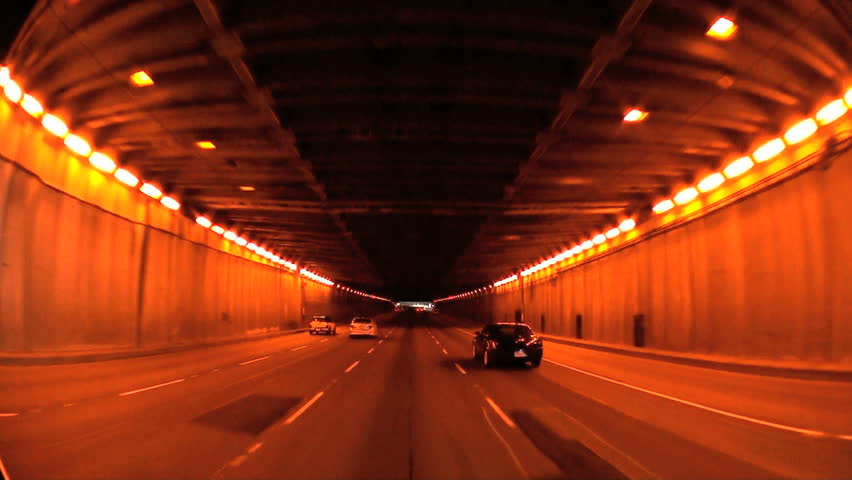 Point-of-view driving through lighted entrance tunnel onto lower level of 5-lane road bridge