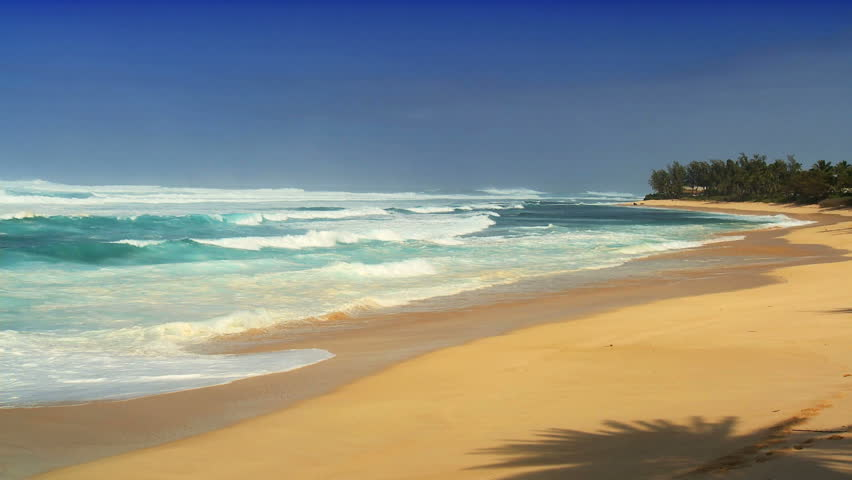 Breaking waves in shallow water onto golden tropical beach