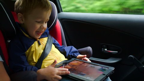 Happy little boy playing game on touchpad sitting in child safety seat in the car