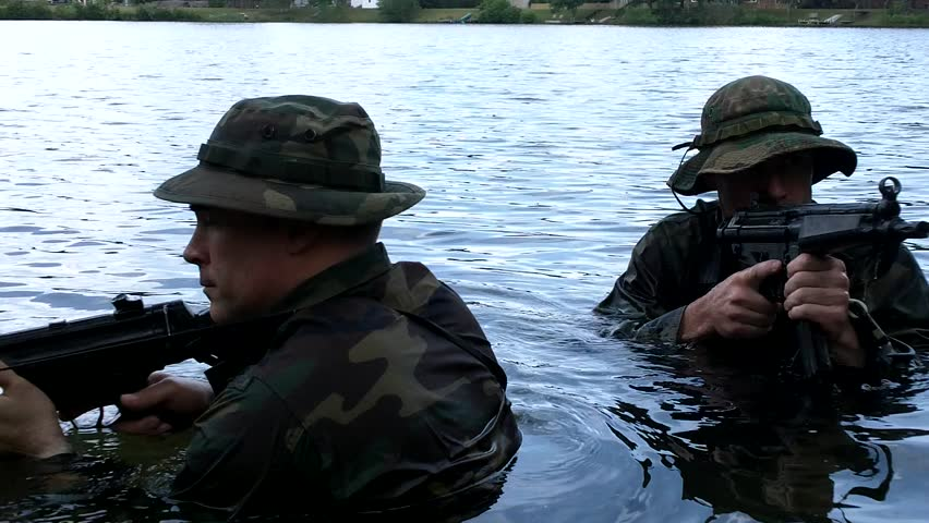 Seal Challenge, Virginia Beach, Virginia Circa 2013: Warrior Students stealthily leave the water with weapons drawn at Seal Challenge, Virginia Beach, Virginia Circa 2013