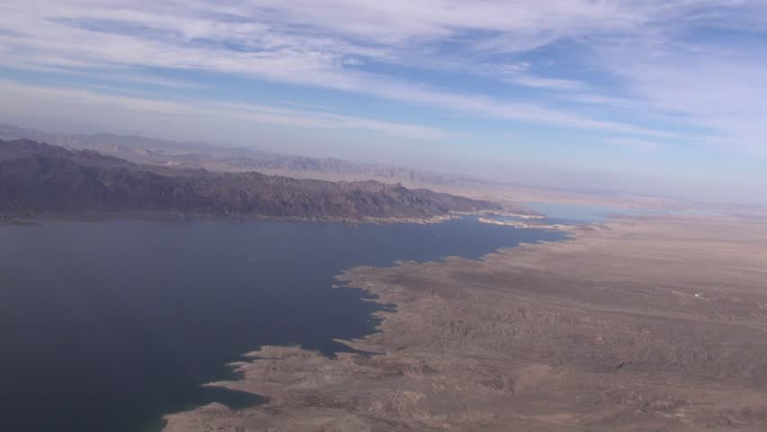 Lake Mead is a tourism areas in Nevada, the largest man-made lake in the world.   Behind Hoover Dam, we pan over Calville Bay.  Lake Mead's water levels are shrinking at drastic levels. | Shutterstock HD Video #6797536