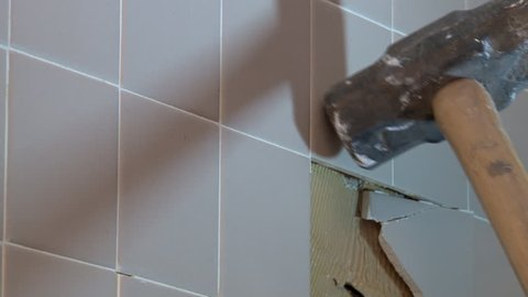 Close up view of sledge hammer pounding and breaking ceramic wall tile during shower renovation project.