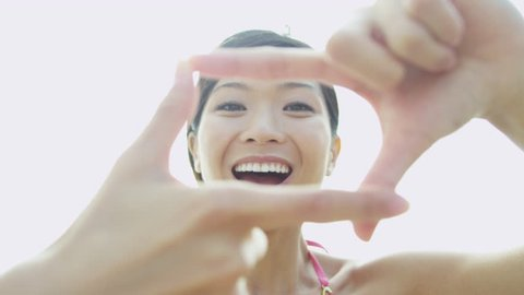 Portrait beautiful smiling young Asian Chinese girl close up fingers making hand picture frame post on social media sites shot on RED EPIC
