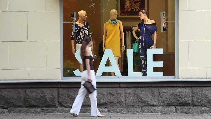 Sale. Young attractive woman stopping to marvel shop window and is looking at mannequins.