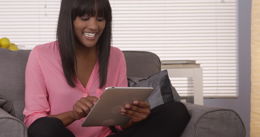 Video of a woman sitting on a sofa while using an ebook stock pretty black woman using tablet in pink shirt 4k stock video clip fandeluxe Ebook collections