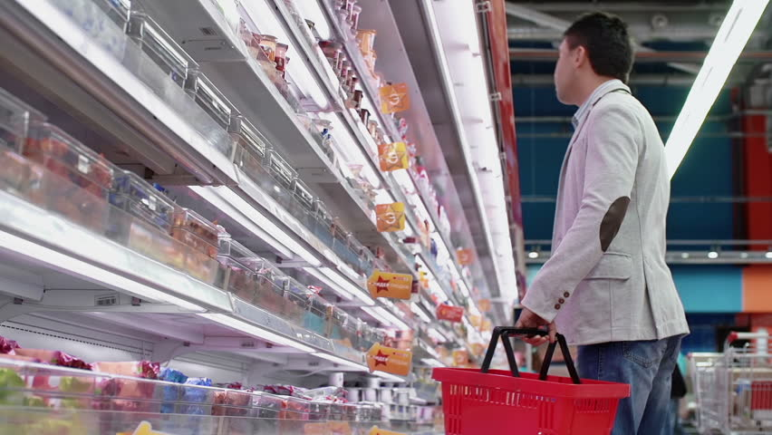 Low angle of guy shopping in dairy products department