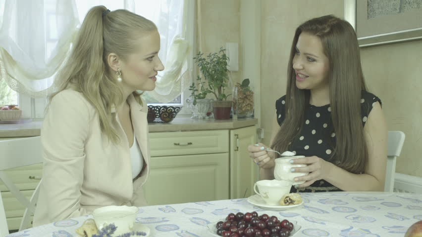 Portrait of two smiling young women having tea at dining table. Two  Caucasian friends chatting and watching magazine at home. Beautiful  interior design. 4a16fba52