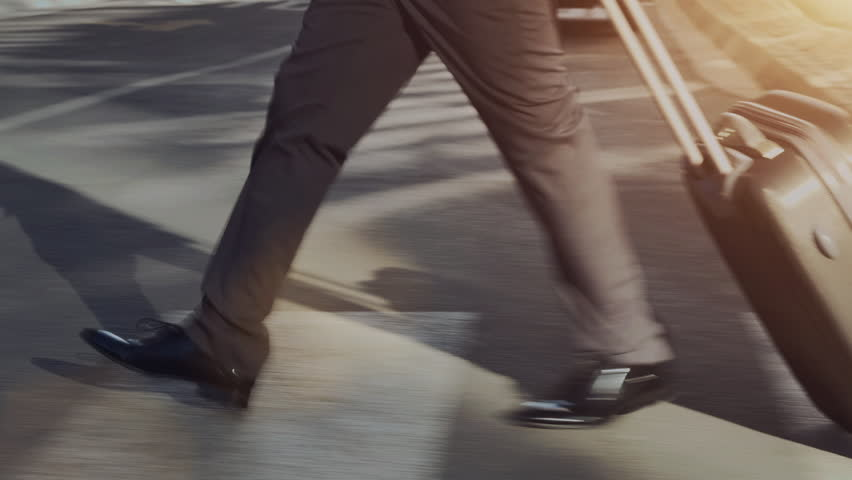 Steadicam shot of African American business man with laptop bag while commuting to work or airport as he walks in a modern city street at sunrise.    Shutterstock HD Video #6845416