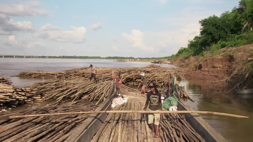 Cambodia - october 2012. Workers moving bamboo poles stored in water and laying them width wise across a barge tied up at the riverbank (view from the bow of the barge), - HD stock video clip