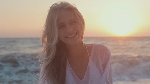 Young seductive girl with long hair in a white tunic smiling and plays the fool at sunset near the sea
