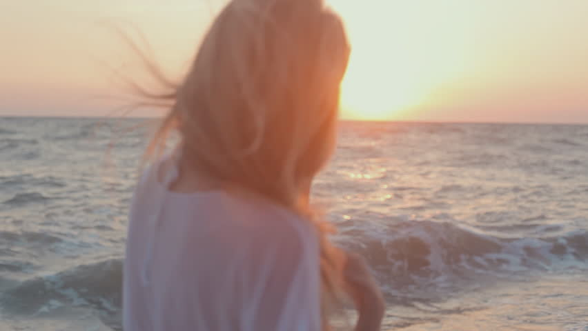 Young seductive girl with long hair in a white tunic stands at sunset near the sea, smile and play fool
