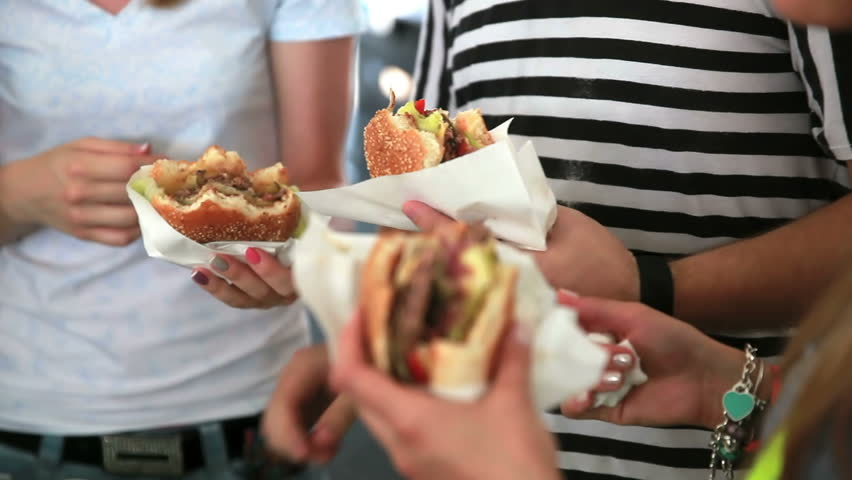 Young people eat burgers and fries on the street | Shutterstock HD Video #6921064