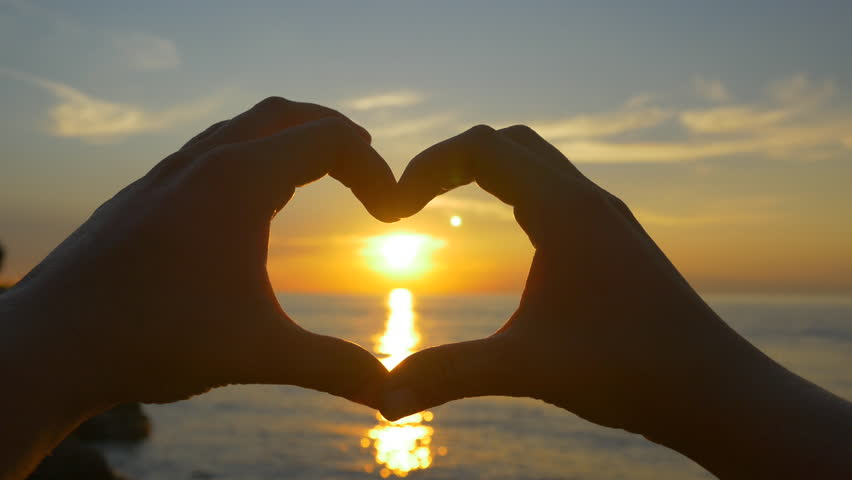 Capturing ocean sunset with heart shaped hands