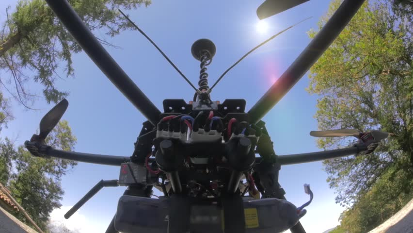 Preparing helices of professional drone before take off on a forest.