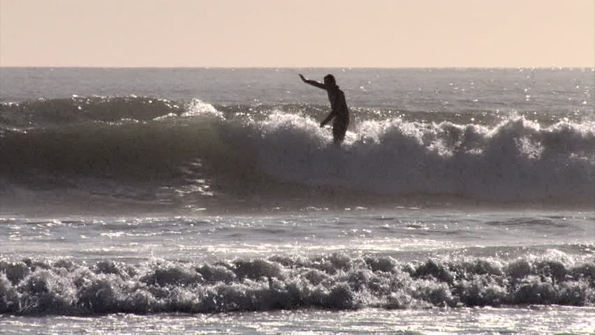 A surfer nose rides on a longboard whilst hanging ten | Shutterstock HD Video #7047796