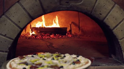 Tracking shot of unidentified cook placing pizza in wood-fired stove with pizza peel