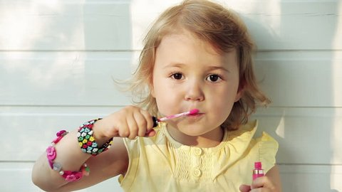 A little girl puts lip balm on her mouth. Children Imitating Adults
