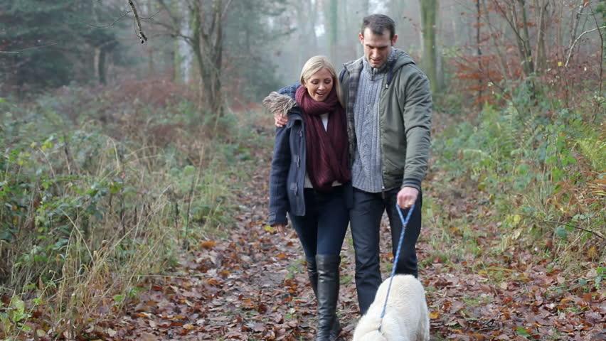 Couple Walking Dog Through Winter Woodland  #7082986