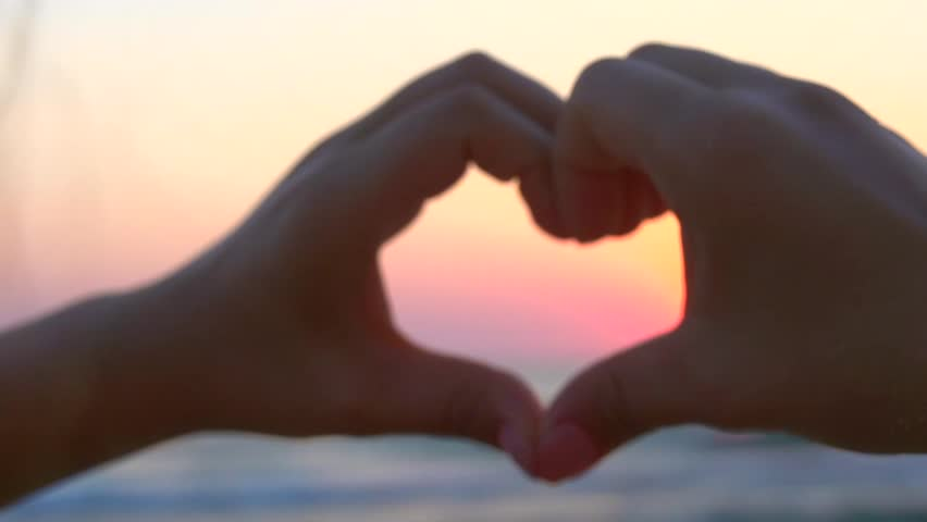 Beauty girl making heart with her hands over sea background. Happy young woman. Silhouette hand in heart shape with sunset inside. Vacation concept. Summer holidays. Tourism. Slow motion 240 fps 1080p