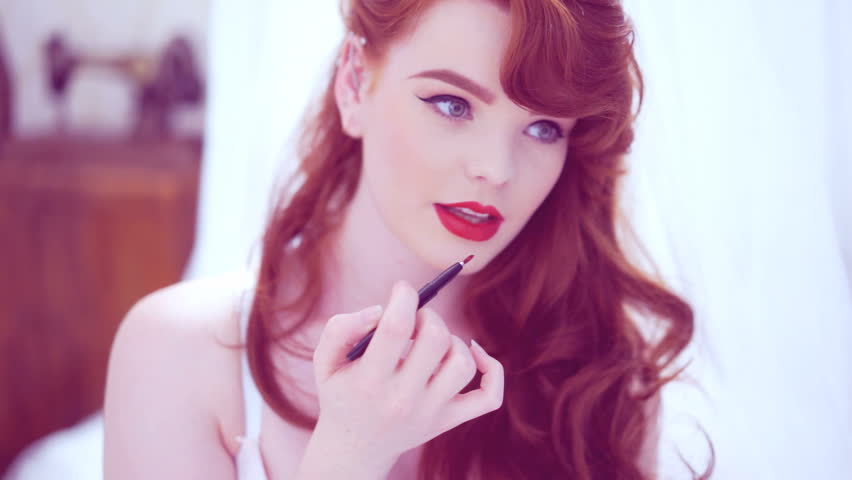 Beautiful young redhead woman with long wavy hair applying red lip gloss or lipstick to her parted lips in a sensual beauty portrait against a filmy white fabric background