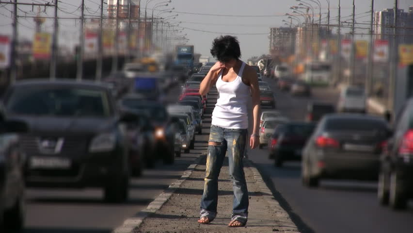 girl dancing on highway middle in city, cars blurred